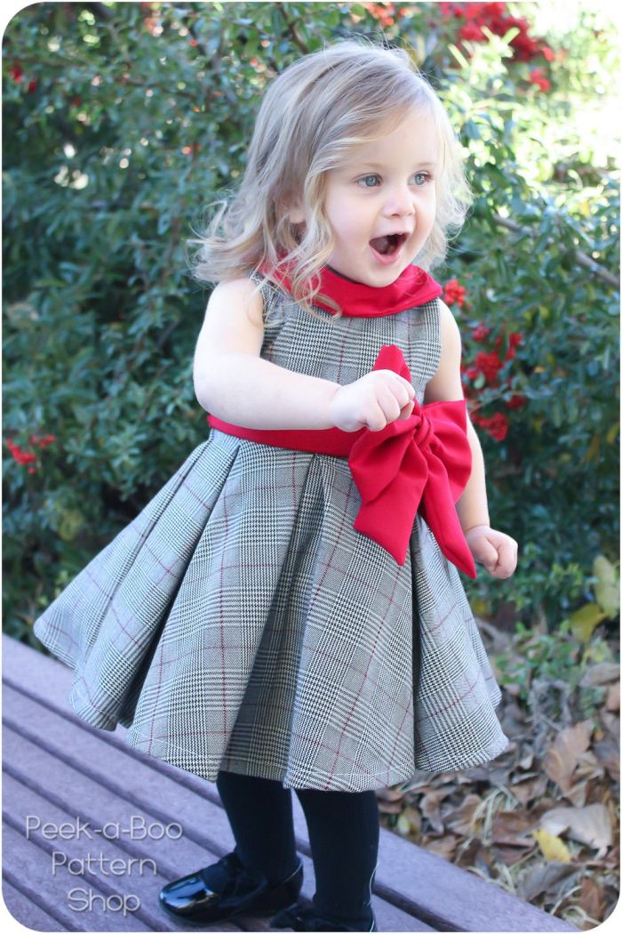 pictured young girl in pleated dress with big red bow