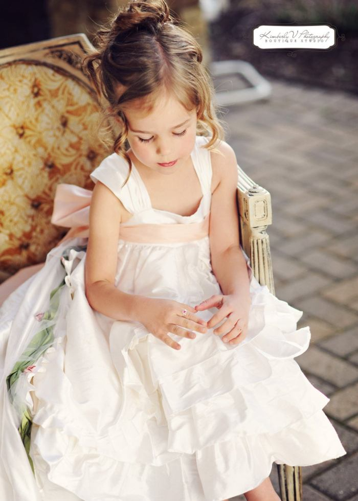 pictured girl in vintage flower girl dress sitting in chair