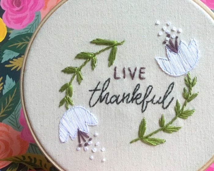 2 white flowers and words live thankful in embroidery hoop