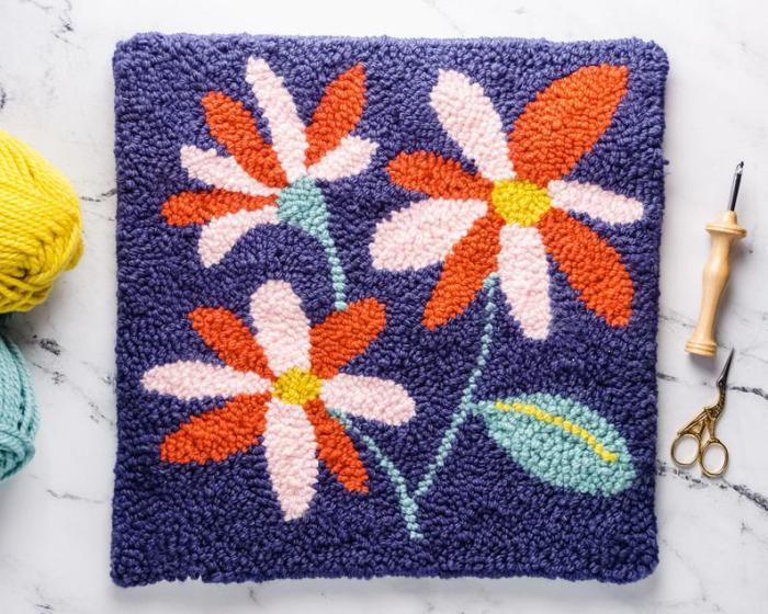teal orange and pink flowers on blue punch embroidery