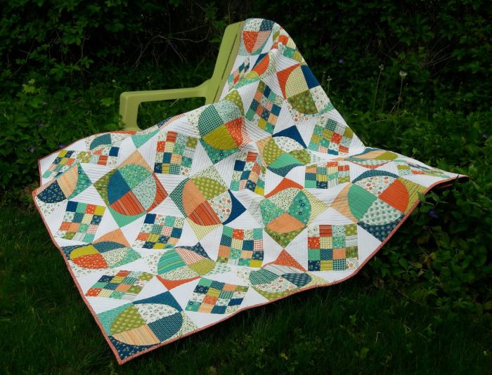 quilt draped over a green lawn chair