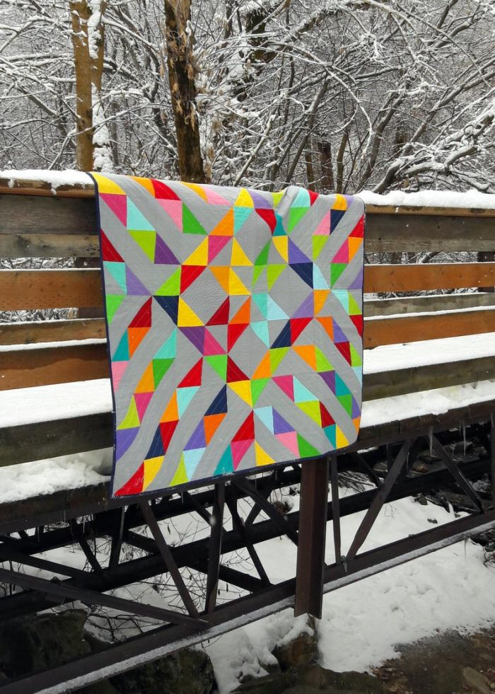 pictured colorful quilt hanging over wooden bridge on a snowy day