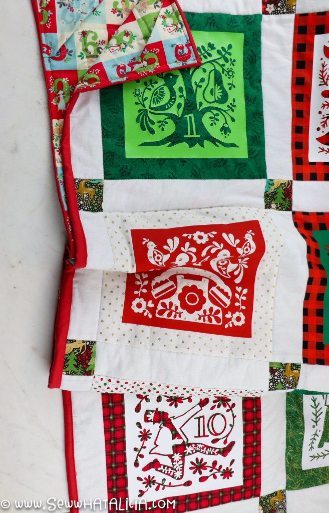 finished 12 days of chirstmas quilt with red binding along edge