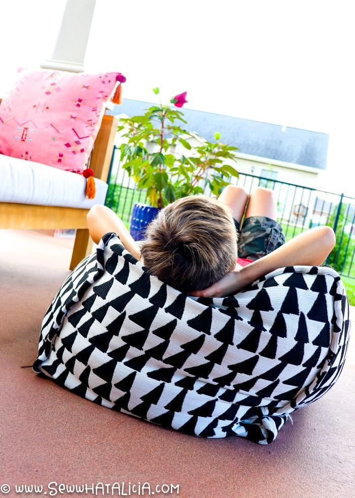 kid lying on top of diy ottoman pouf