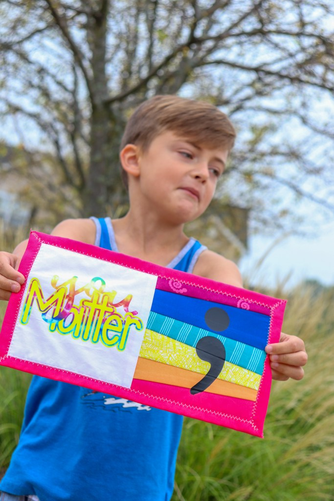 boy holding mini quilt pattern with words you matter and a semi colon on the front