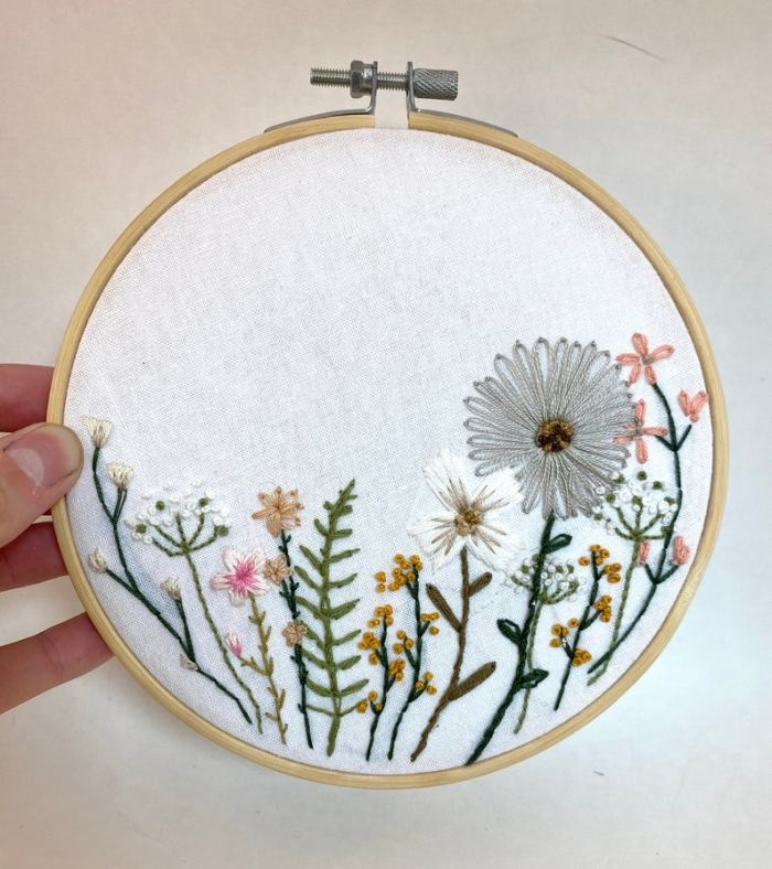 Embroidered floral hoop art held by hand