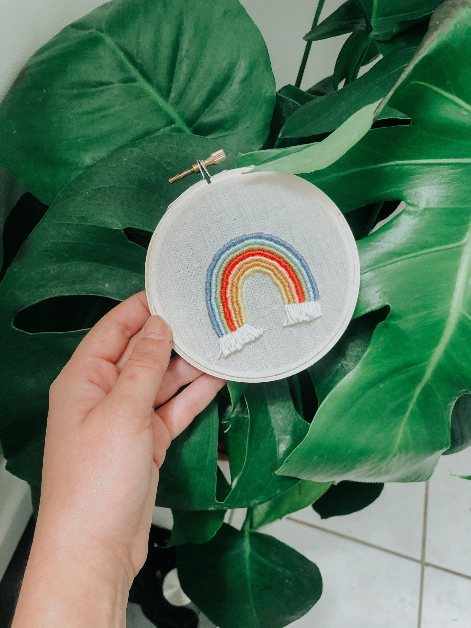 rainbow embroidered on neutral fabric in hoop with leaves in the background