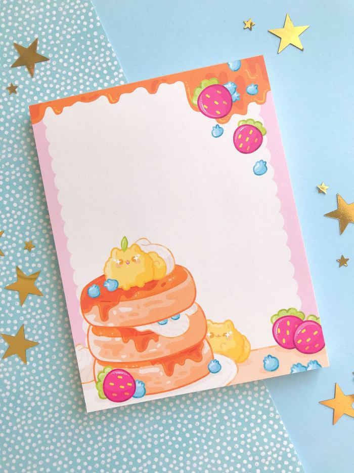 notepad with pancakes and two tiny pomeranians