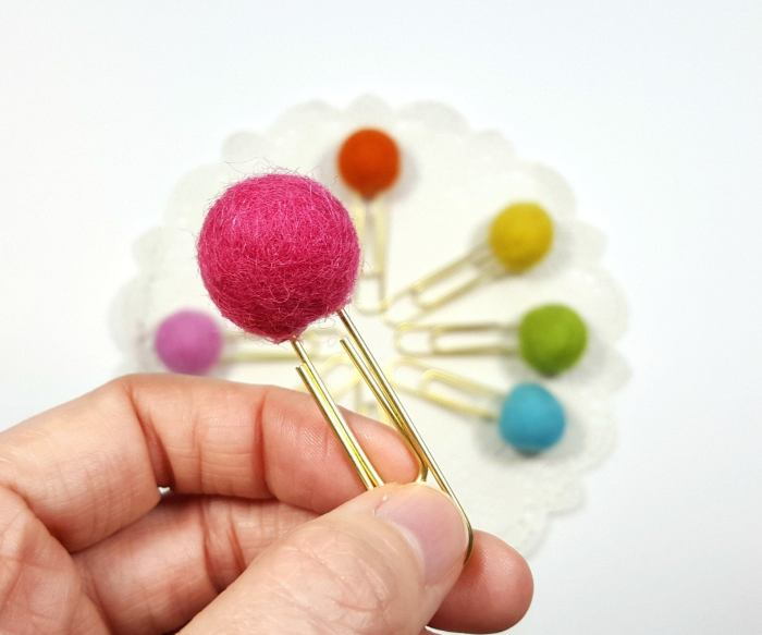 hand holding paperclip with felt ball on top