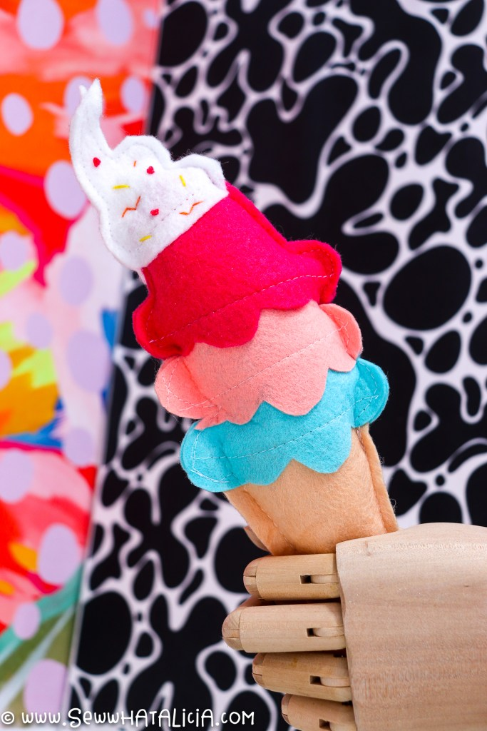 wooden hand holding ice cream cone with colorful background