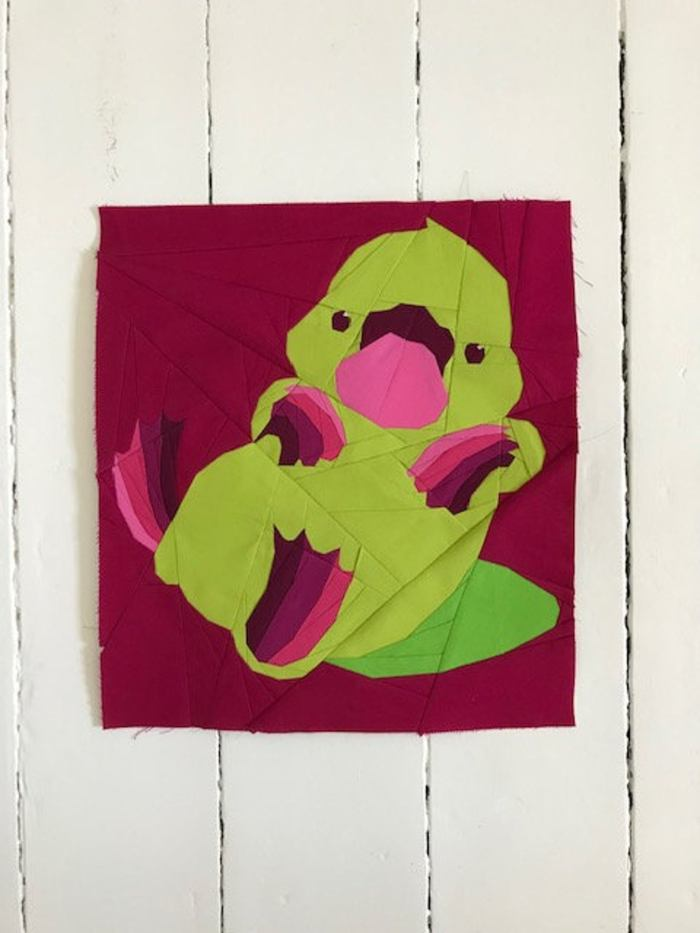 paper pieced platypus quilt block on white wood board background