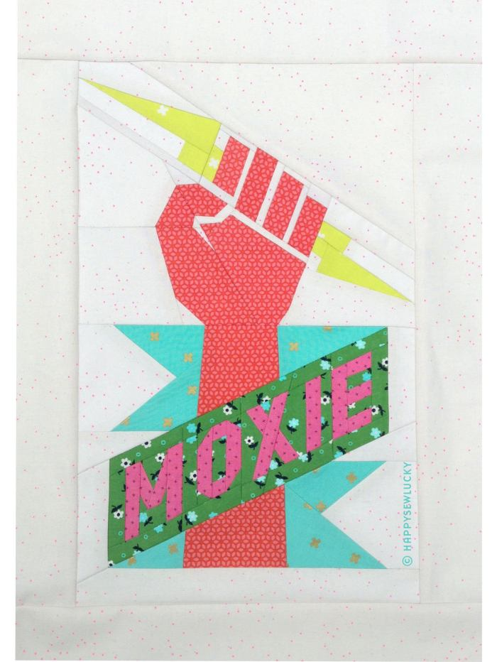 pieced quilt block with hand holding lightning bolt and word moxie on a banner
