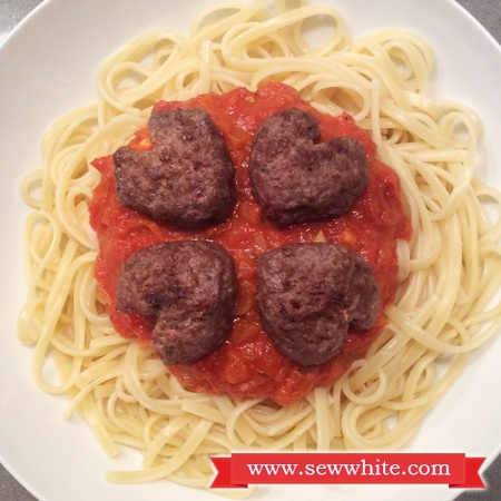 the finished Heart Shaped Meatballs on a bed of tomato pasta sauce