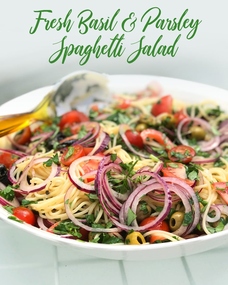 fresh basil and parsley spaghetti salad with raw onion, olives and tomatoes
