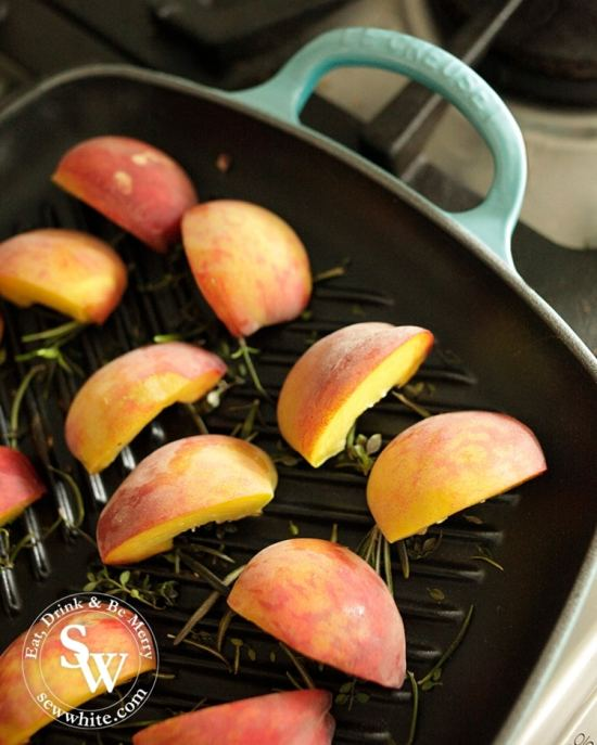 Fresh peaches on a Le Creuset grill pan with fresh thyme and rosemary.