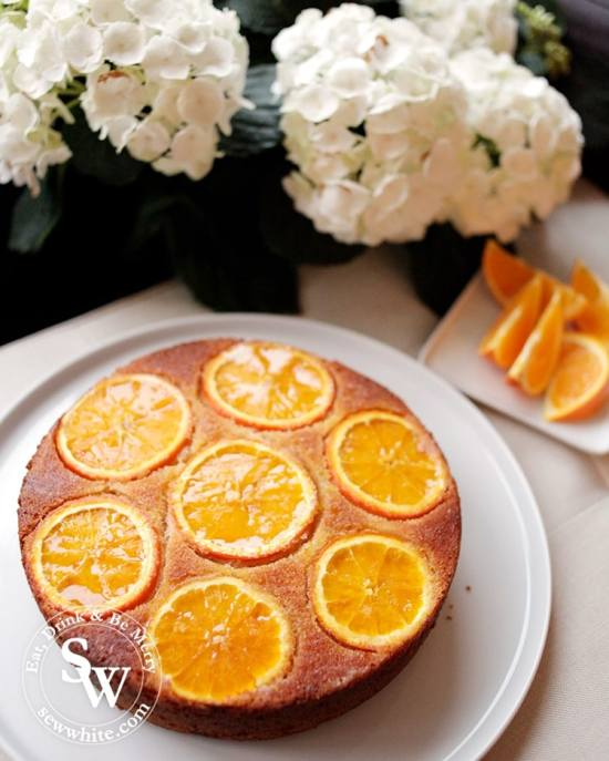 Orange upside down cake fresh out of the oven best served warm. Orange Drizzle Cake made with fresh orange juice on a while plate