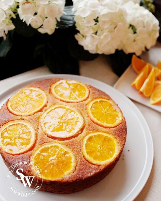 Glistening Orange Drizzle Cake next to white flowers