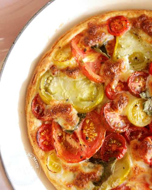 Puff Pastry Tomato Tart with a mix of large and small tomatoes baked with golden brown mozzarella on top.