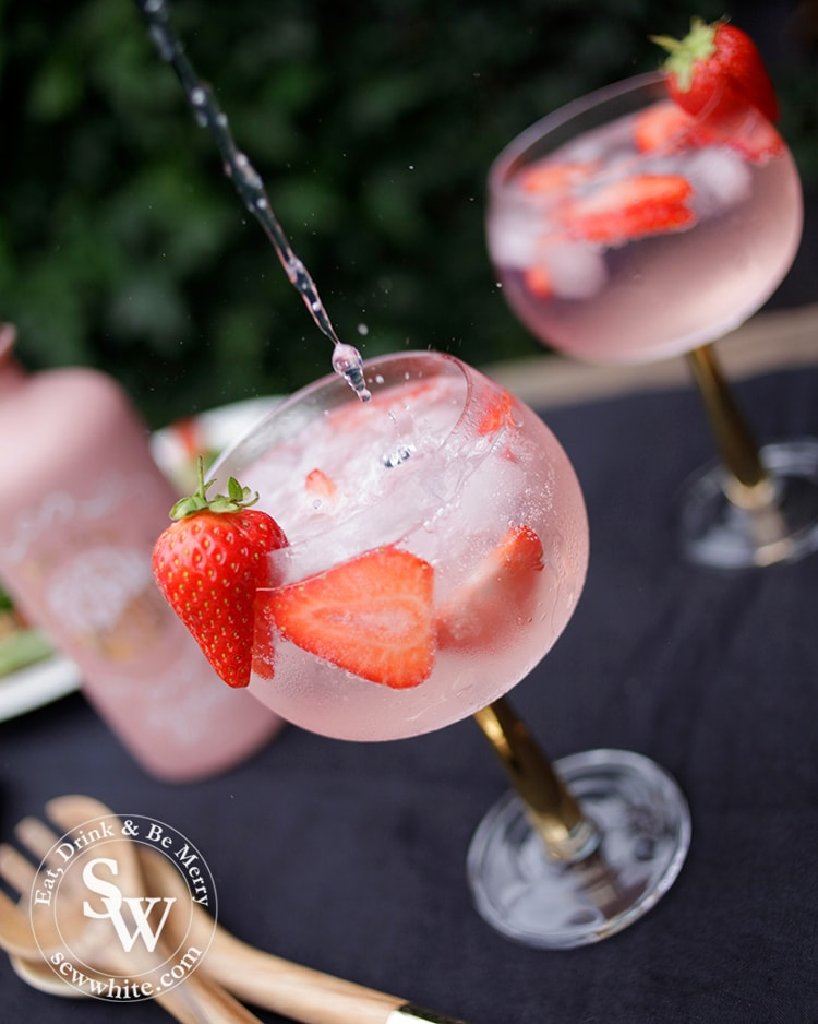 Fever tree tonic being poured in to the gin balloon glass with strawberries inside.