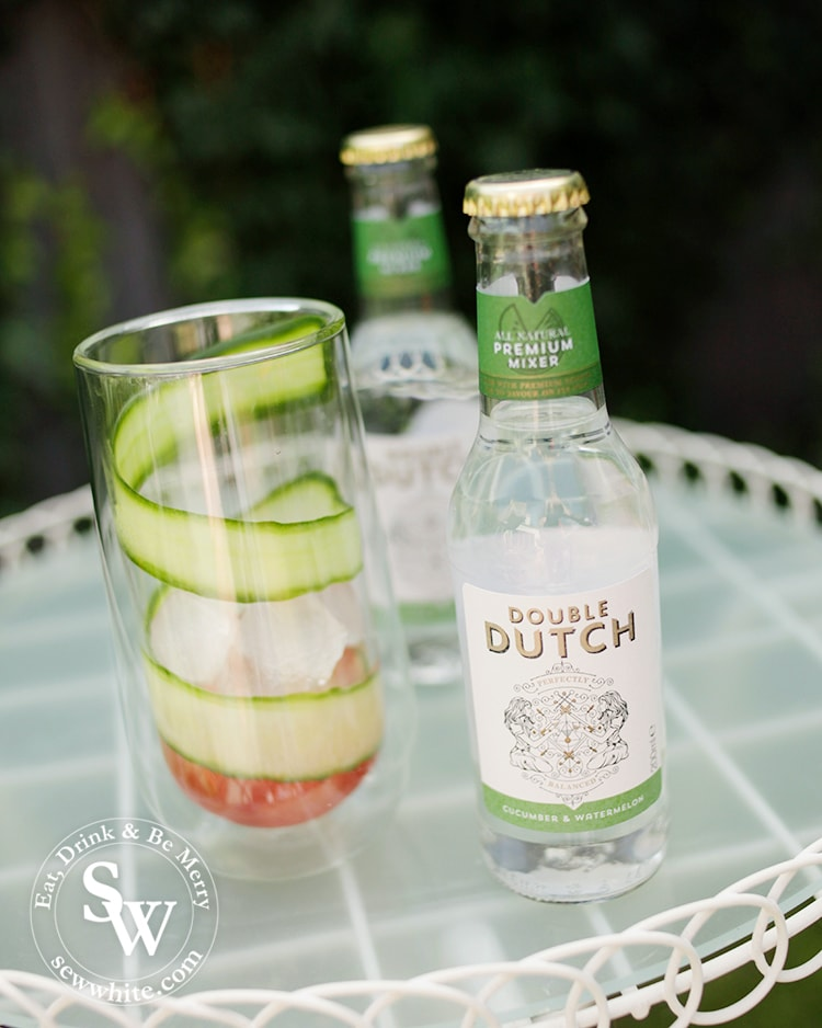 A double walled glass with a thin slice of cucumber wrapped around the glass in a swirl with fresh watermelon juice in the bottom. With a bottle of Watermelon and Cucumber Rum Punch by Double Dutch.