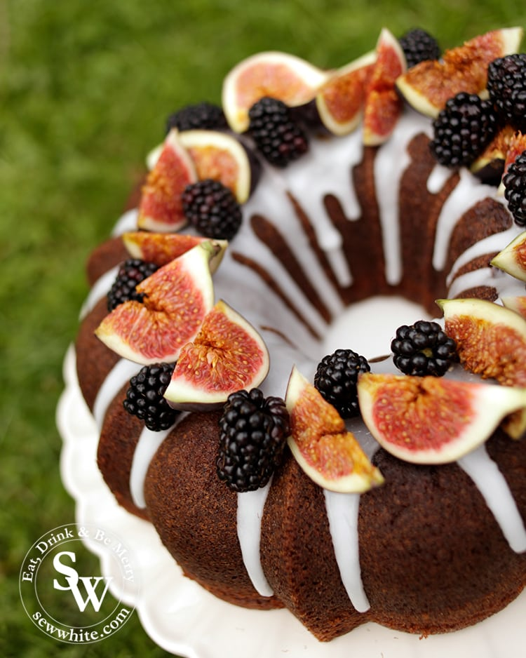Autumn Cake topped with blackberries and figs on a cake plate
