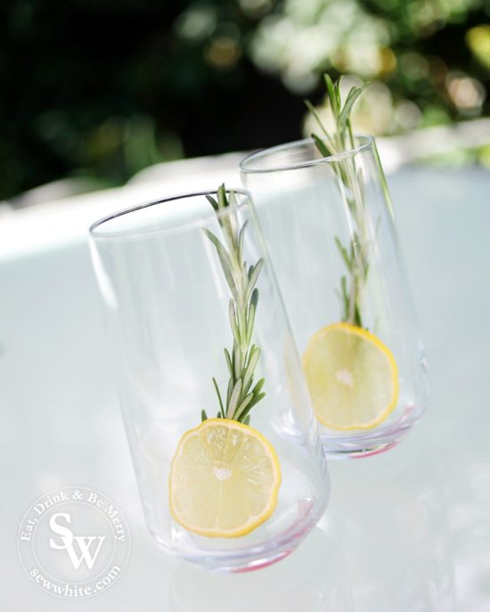 A slice of bright yellow lemon and large green sprig of rosemary.