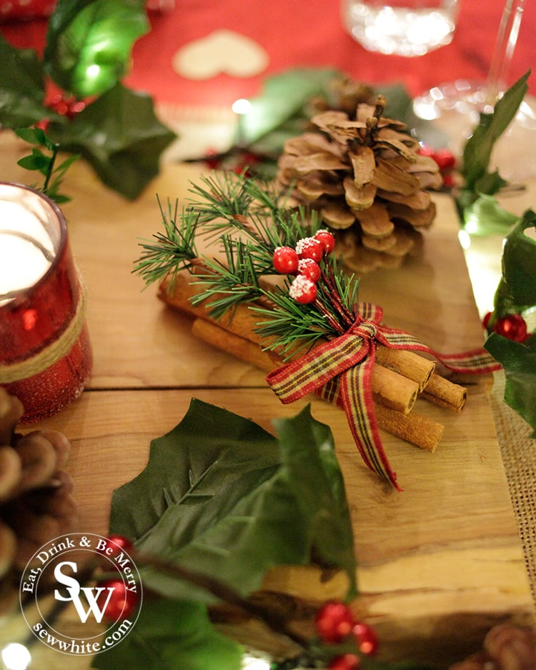 Finishing touches on the Red and Green Woodland Christmas Table with bundles of cinnamon sticks and pine cones.