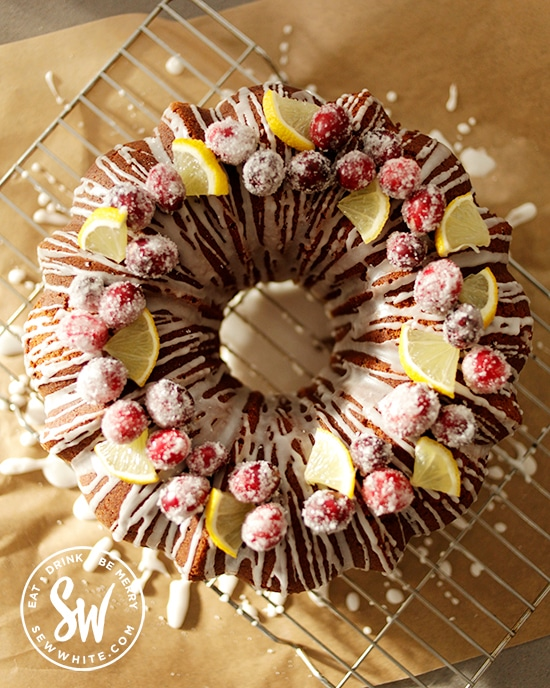 Cranberry bundt cake topped with sugared cranberries and lemon slices