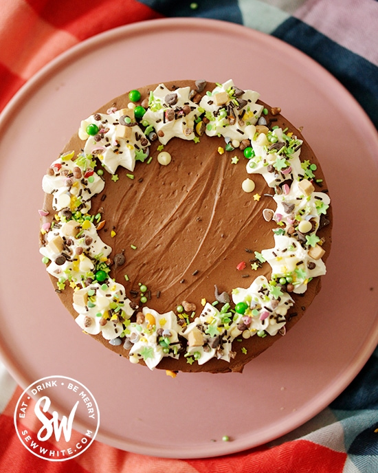 Guinness cheesecake with white cream top decorated with green sprinkles to make it give a hint of Ireland