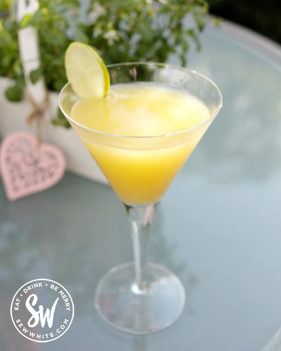 A golden cocktail glistening in the sunshine made with malibu and vodka