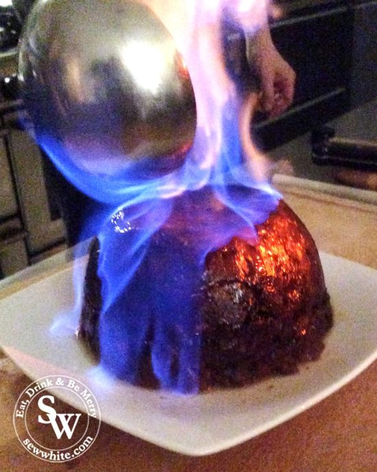 A homemade Traditional Christmas Pudding on fire with blue flame and about to be served.