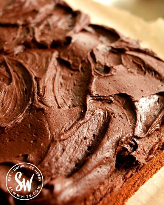 Close up of chocolate cream cheese buttercream on the ultimate chocolate traybake