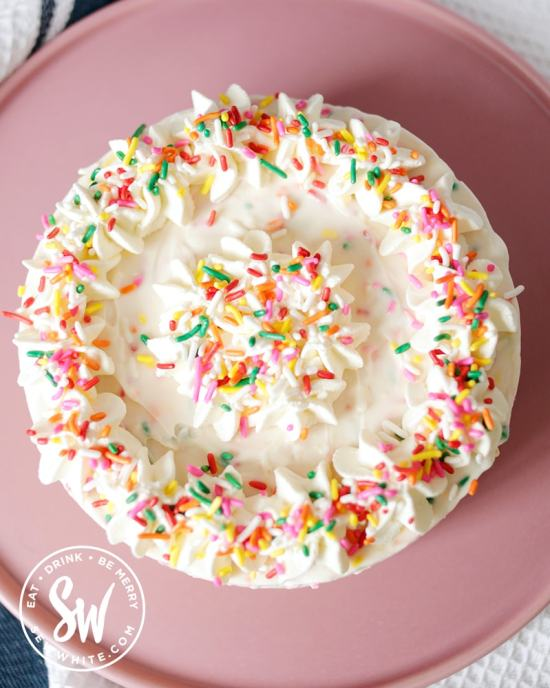 Funfetti Cheesecake decorated with even more brightly coloured rainbow sprinkles.