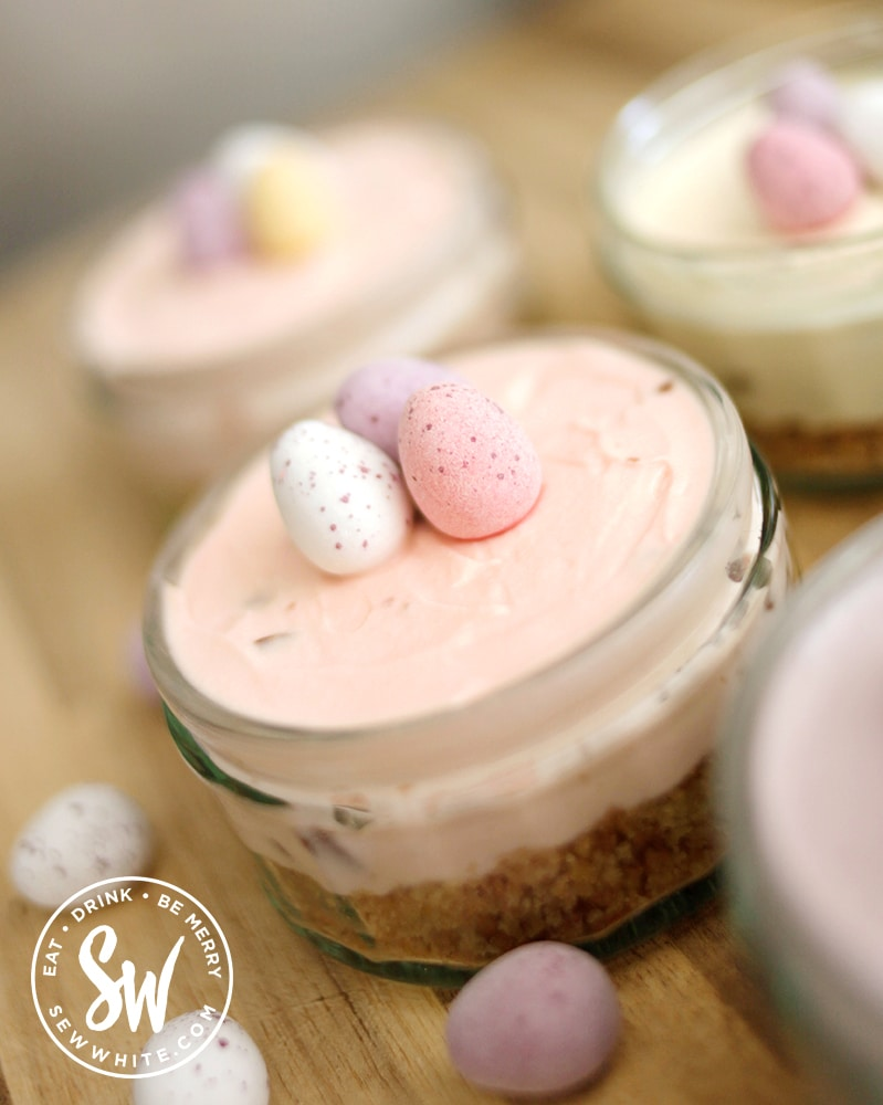 pastel pink mini cheesecakes with mini eggs on tops.