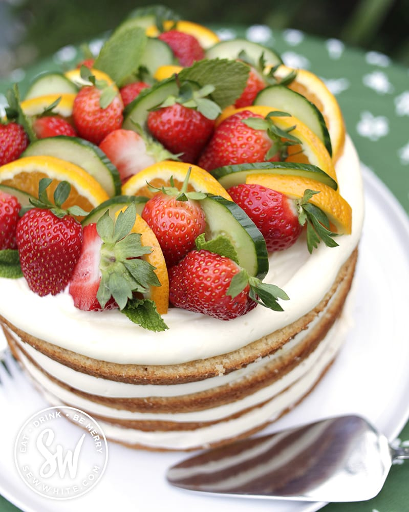 the top of the pimms cake with lots of pimms fruit includnig strawberries, orange and cucumber