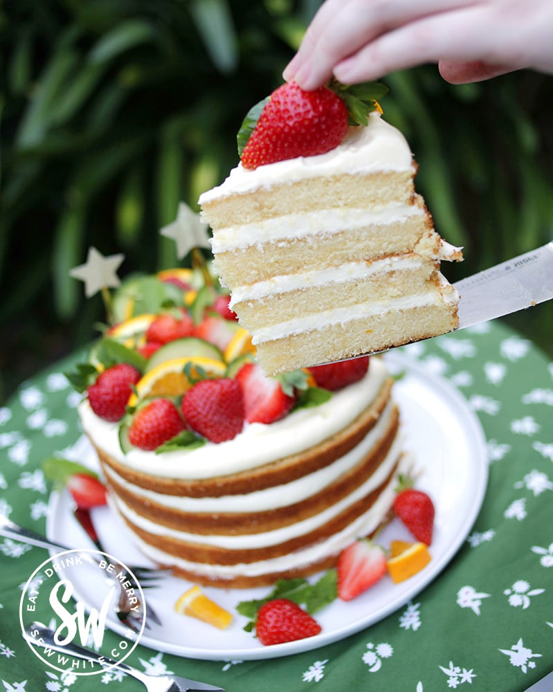A slice of pimms cake with 4 layers of cake and cream cheese buttercream