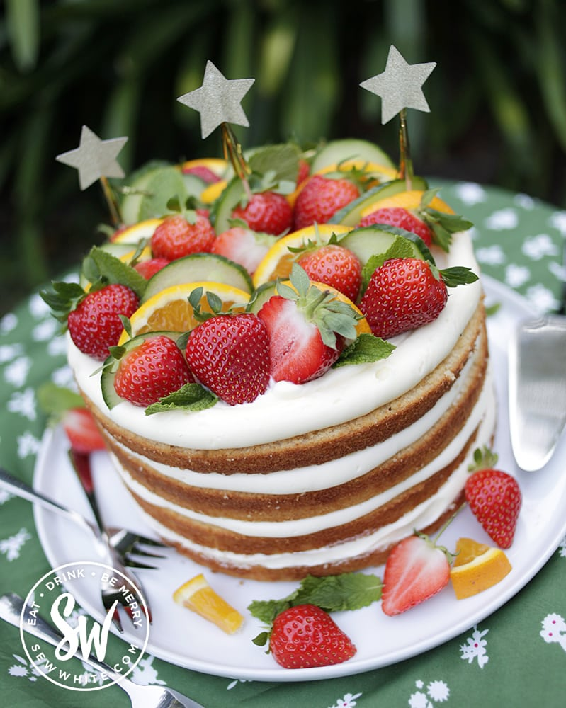 Pimms drizzle cake decorated with strawberries, oranges, cucumber and fresh mint and start sparklers