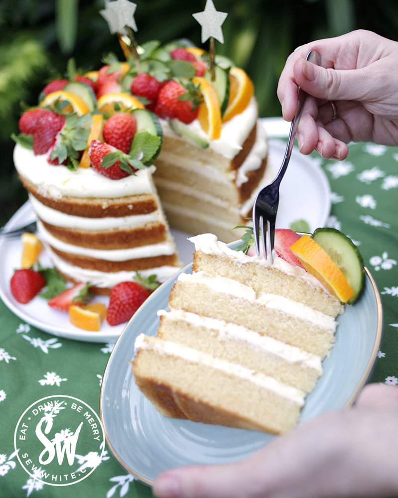 A close up slice of layer cake made with Pimms and the pimms cake in the background