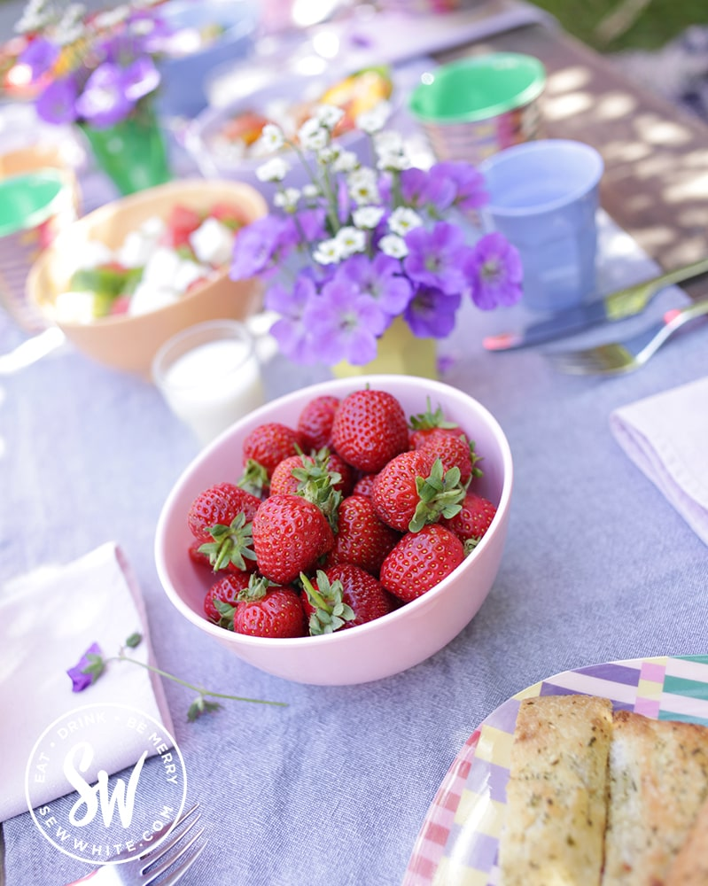 fresh strawberries in a pink bowl on a blue table - pimms salad / pimm's salad