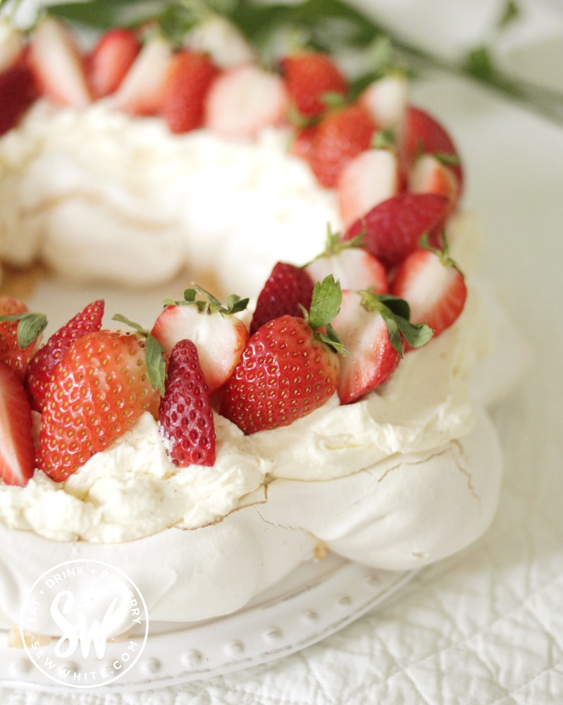 strawberries on a cream layer and meringue base - Strawberry Passionfruit Pavlova