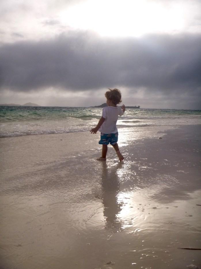 Family walk. Throwing stones in the ocean