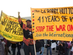 """Banners at the """"Defend African People's Right to Resist"""" march and rally on MacArthur Boulevard Wednesday recalled the long history of Oakland police murders of young Black men. – Photo: Dave Id, Indybay"""
