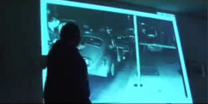 "At a press conference in Philadelphia Dec. 4, 2007, Hans Bennett shows slides of the Pedro Polakoff crime scene photos. This one, known as ""The Moving Hat,"" shows Officer Faulkner's hat on the top of Billy Cook's VW. For the official police photo, it had been placed on the sidewalk. – Photo: Journalists for Mumia video"