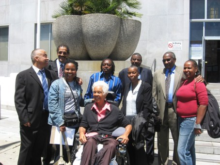 """Outside the courthouse on July 6, San Francisco 8 members and supporters celebrated the dismissal of all charges against all the defendants who had been out on bail except Francisco Torres – Cisco himself joining in the jubilation. In the back row, from the left, are SF 8 members Francisco Torres, Ray Boudreaux, Richard Brown, Harold Taylor and Hank Jones and supporter Nadra Foster. In the middle row are Wanda Sabir and Soffiyah Elijah and, in front, Kiilu Nyasha. During the hearing that day, fellow SF 8 defendant Jalil Muntaqim, who remains a political prisoner (see """"Letters of support needed immediately for Jalil Muntaqim's parole hearing""""), self-sacrificially negotiated a plea arrangement with the prosecutor, California Attorney General Jerry Brown, to free his SF 8 brothers. – Photo: Wanda Sabir"""
