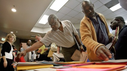 Johnnie Daniels and Kerwin Barber search through job listings at a job fair Los Angeles. The Black unemployment rate is officially 15.7 percent nationwide, compared to 9.5 percent for whites. But even Fox News reported Nov. 18 that in some communities half of Black men are out of work. - Photo: Ric Francis, AP