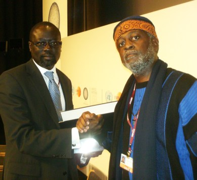 Baba Jahahara gives a copy of the Klimaforum09 People's Summit Declaration to G77 coordinator Lumumba Di-Aping.