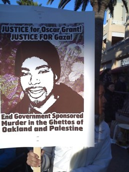 A protester at the Jan. 7 rally at the Fruitvale BART station in East Oakland carries a sign that ties the police execution of Oscar Grant to the Israeli executions in Gaza. - Photo: Dave Id, IndyBay
