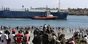 "Kenyans watch the huge freighter MV Faina enter the port of Mombasa, Kenya, last month after the Israeli-owned ship, loaded with tanks and other heavy weaponry reportedly destined for Israeli-backed ""rebels"" in Darfur, was ransomed and released by Somali ""pirates,"" who had held it for four months. – Photo: Antony Njuguna, Reuters"