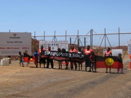 On the Burrup Peninsula, Black Australians stand bravely blocking the gates erected by Woodside, a joint venture of Chevron and Shell, to lock them out of their land. The flags the children are displaying are the Burrups' own – Black for the people, red for the blood they shed trying the protect their land from settlers, yellow – and the red as well – for the ochre they use in the rock art they have been painting for at least 60,000 years.