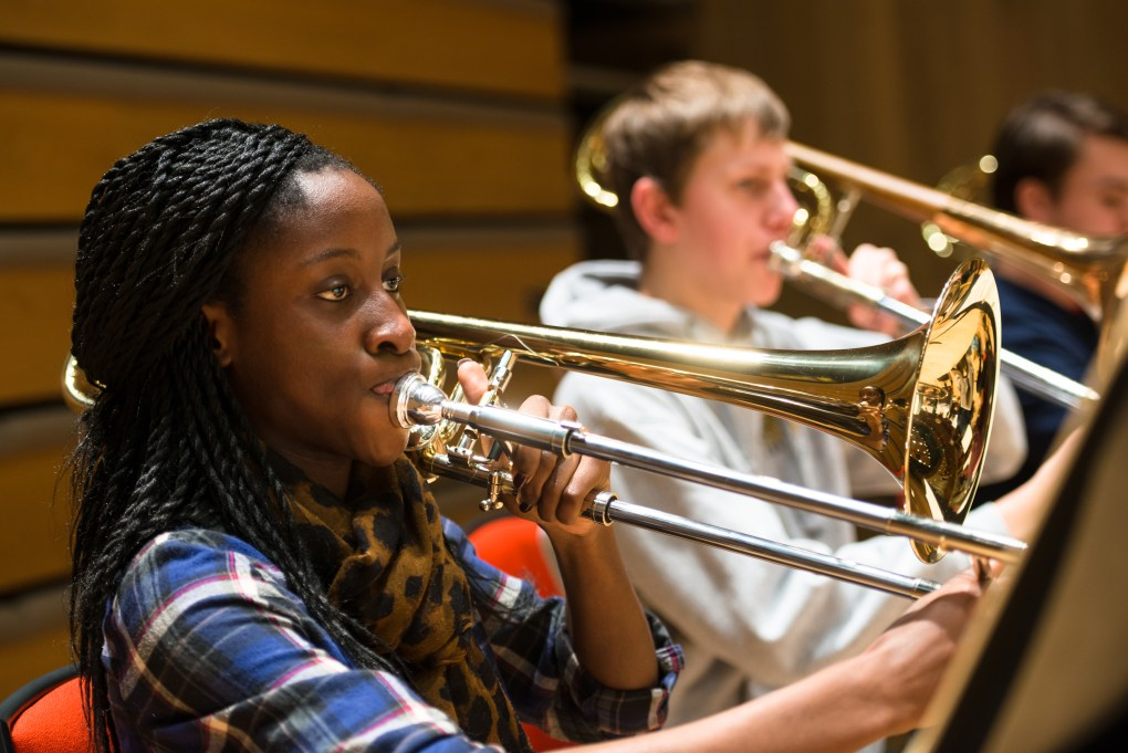 Girl playing trumpet with other trumpet players in the background. Representing wind and brass instrument lessons at SFE Music school